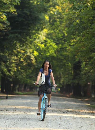 Woman cycling in a park of a city. City Exercise Summertime Transportation Woman Bicycle Cycling Front View Girl Leisure Activity Mode Of Transport Nature One Person Outdoors Park - Man Made Space Real People Ride Riding Summer Transportation Urban Urban Cycling Urban Transportation Young Adult