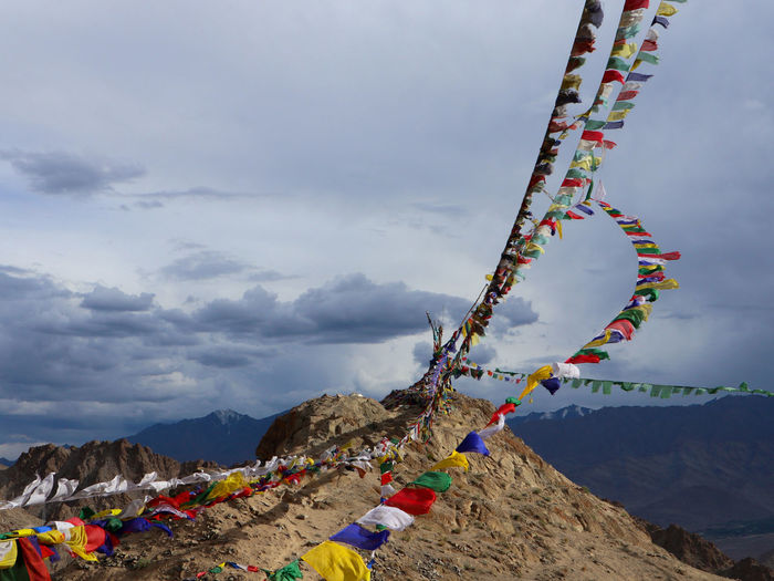 Low angle view of multi colored prayer flags on mountain against sky