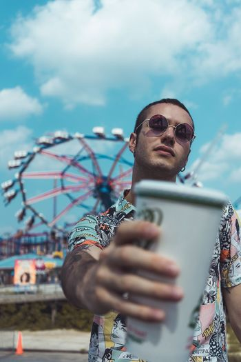 Fun Summer Soda Food And Drink Amusement Park Ride One Person Technology Adult Amusement Park Front View Communication Glasses Arts Culture And Entertainment Wireless Technology Leisure Activity Sky Men Cloud - Sky Connection Ferris Wheel Sunglasses Holding Portrait Outdoors
