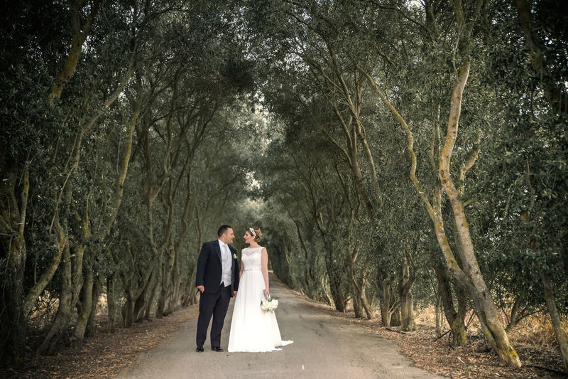 Adult Bride Bridegroom Celebration Couple - Relationship Emotion Event Forest Full Length Love Newlywed Outdoors Plant Positive Emotion Rear View Togetherness Tree Treelined Two People Wedding Wedding Dress Wife Women