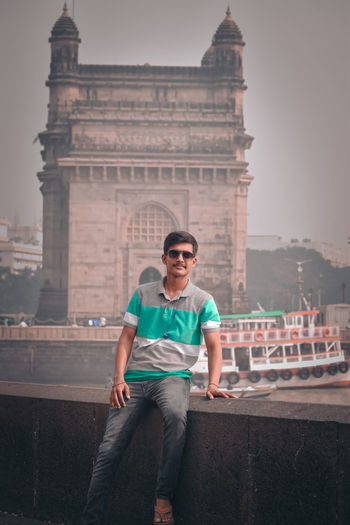 Full length of young man against sky in city near the gateway of india