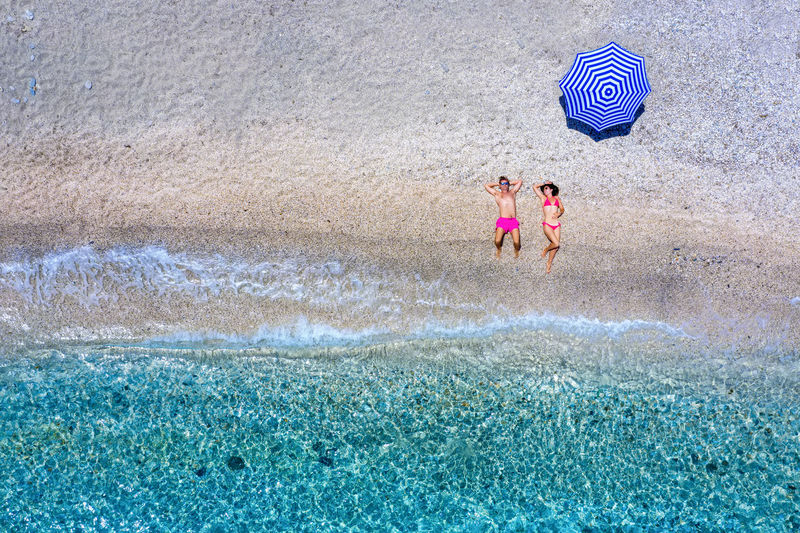 Aerial view of couple lying at beach on sunny day