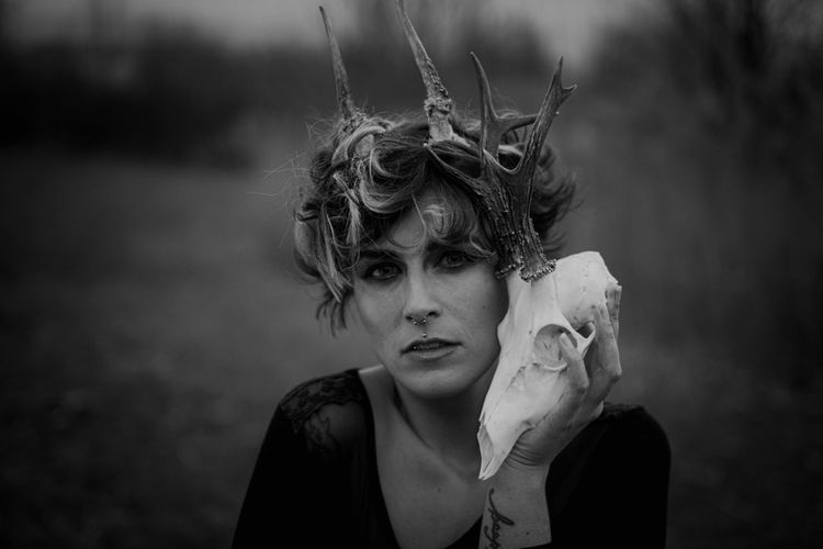 Portrait of woman with horns holding animal skull in forest