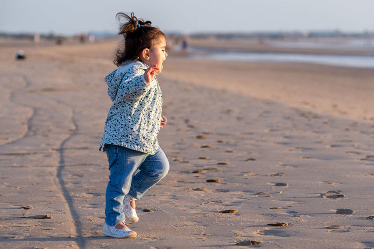 Side view of baby girl with mouth open standing at beach during sunset