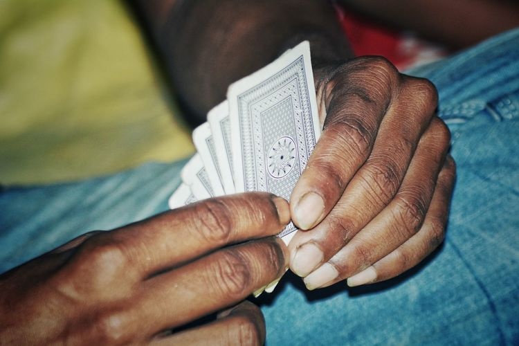 Cropped hands holding playing cards at home