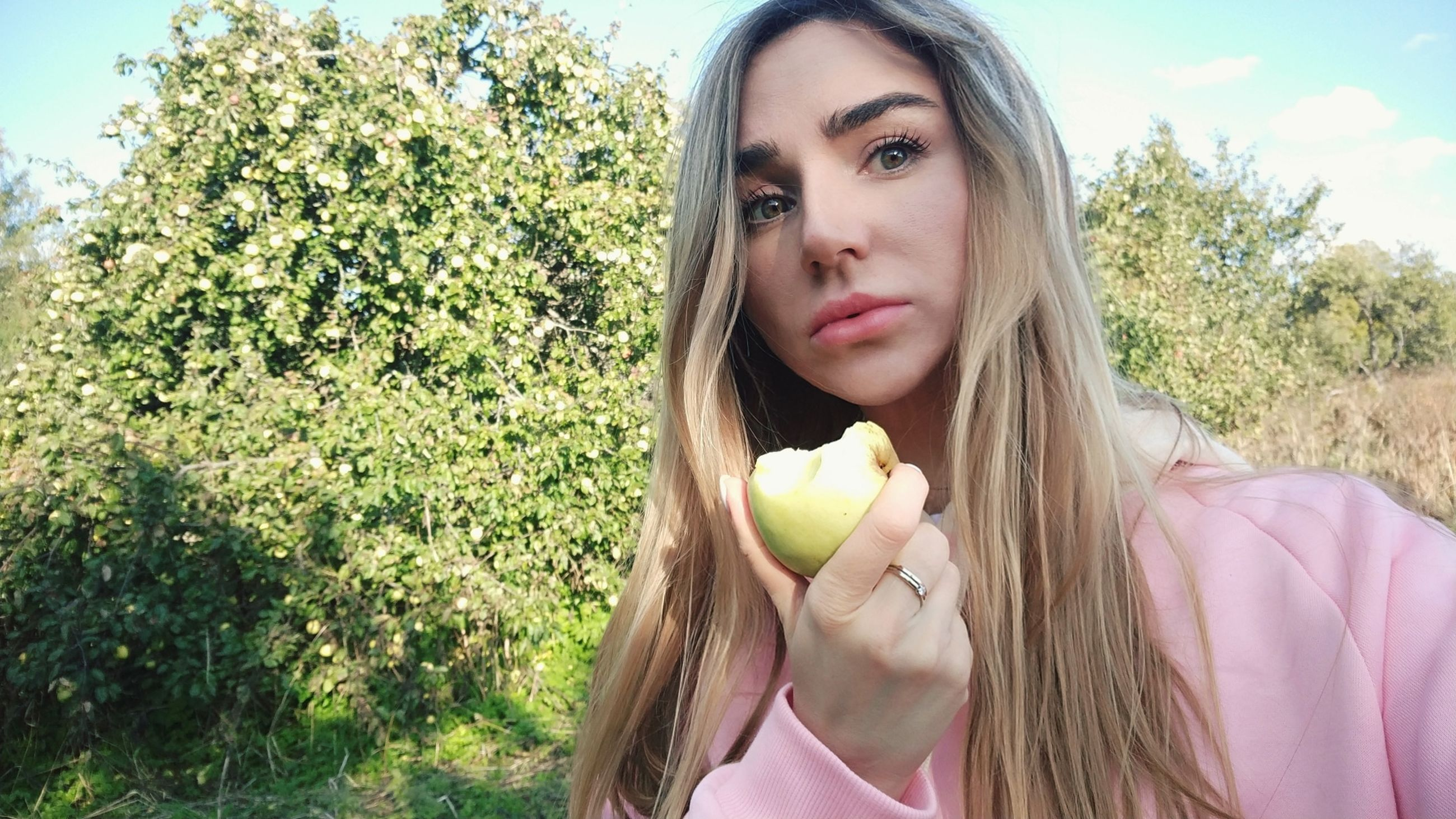 portrait, plant, real people, fruit, front view, one person, young women, leisure activity, hair, young adult, lifestyles, food and drink, looking at camera, healthy eating, headshot, day, long hair, food, holding, hairstyle, beautiful woman, outdoors