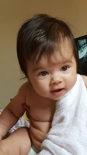 Close-up portrait of cute shirtless baby girl at home