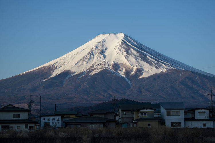 Close-up on Mount Fuji and small village, Japan Yamanashi Winter White Water Volcano View Vacation Travel Town Tourism Sunset Sunrise Summer Spring Snow Sky Season  Scenic Scenery Scene Peak Outdoor No People Nature Natural Mt Fuji MT Mountains Mountain Mount Morning Landscape Landmark Lake Japanese  Japan Ice Holiday Grass Fuji Fresh Evening Dusk Destinations Dawn Blue Beauty Beautiful Background ASIA