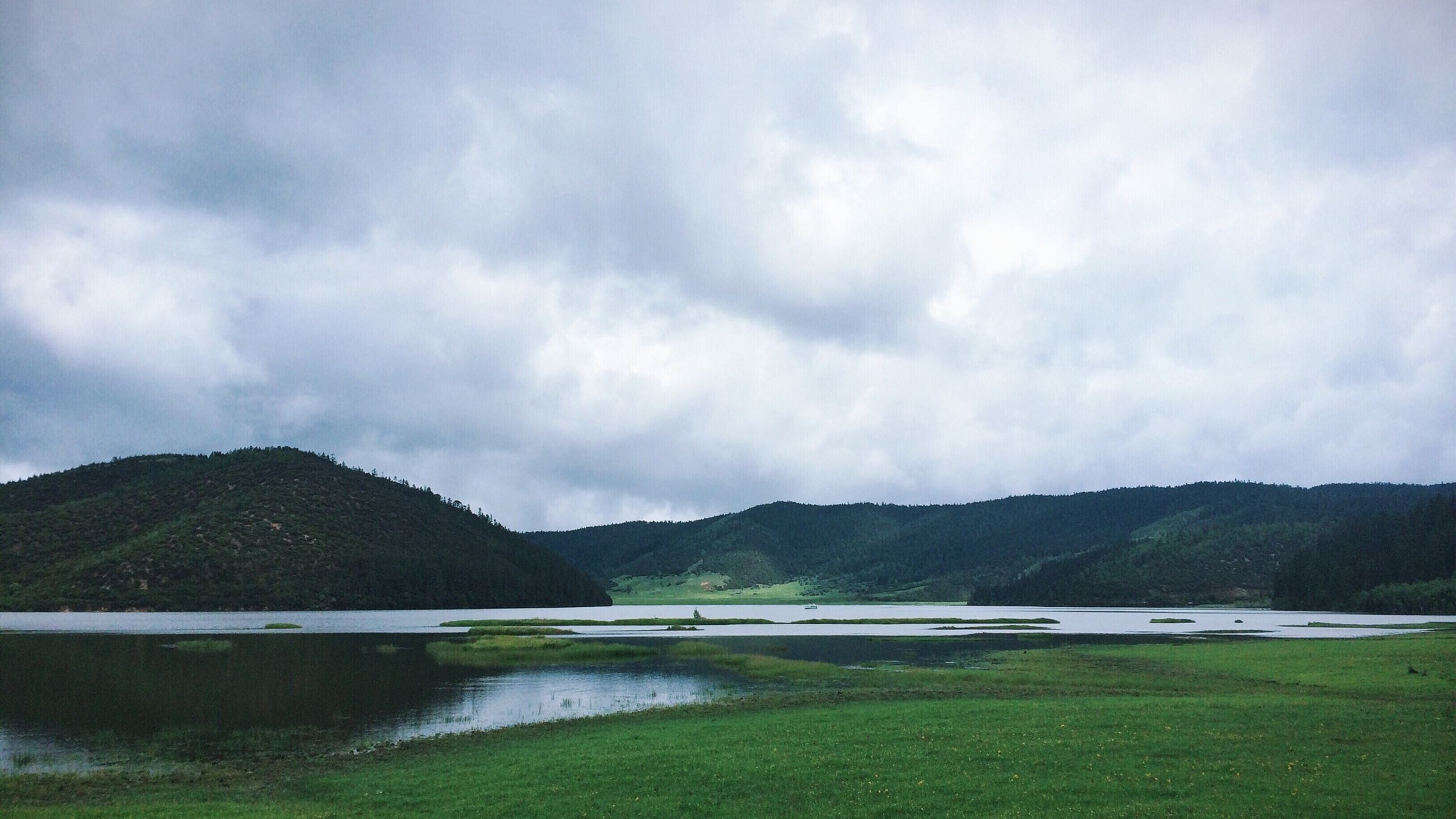mountain, water, sky, mountain range, tranquil scene, lake, tranquility, scenics, cloud - sky, beauty in nature, cloudy, nature, cloud, river, idyllic, landscape, non-urban scene, day, lakeshore, grass