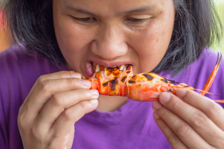 Close-Up Of Woman Eating Lobster