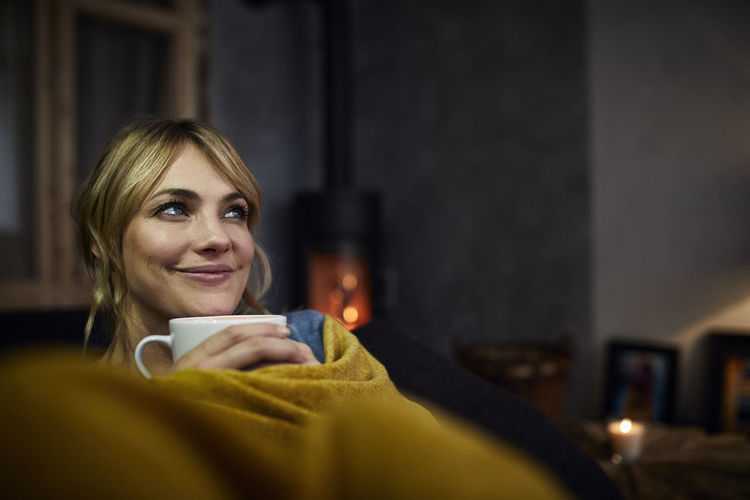 Portrait of smiling woman holding coffee cup