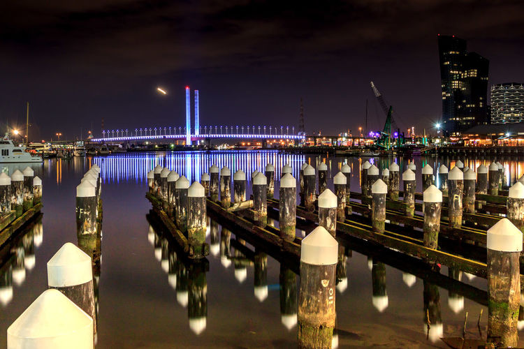 The West Gate Bridge surrounded by pillars in the Docklands Architecture Bridge Bridge - Man Made Structure Building Exterior Built Structure City Connection Illuminated Light Nature Night No People Pier Post Reflection River Sky Transportation Travel Destinations Water Wooden Post