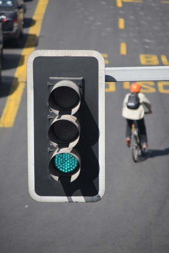 High angle view of illuminated green light against man cycling on road