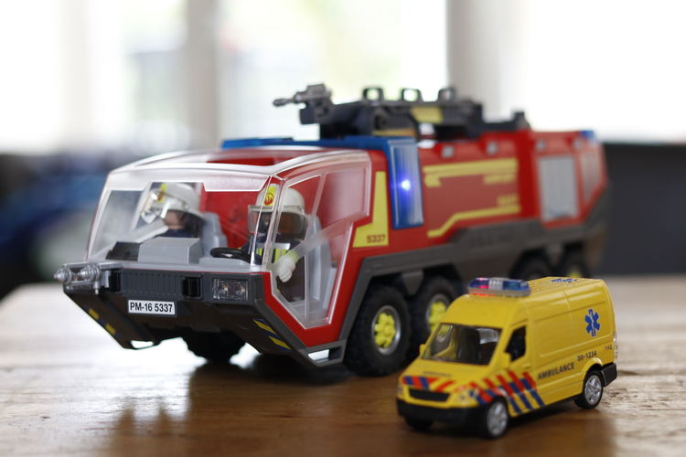 Close-up of toy fire engine and ambulance on table