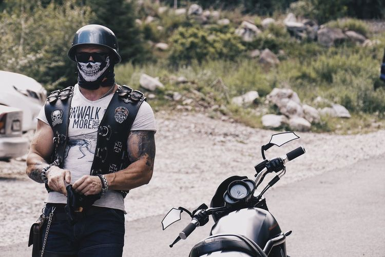 Man wearing mask and helmet standing by motorcycle on road