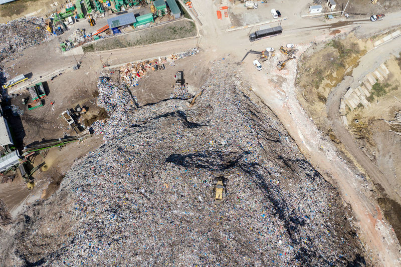 Aerial top drone view of large garbage pile, trash dump, landfill, waste from household dumping site, excavator machine is working on a mountain of garbage. Consumerism and contamination concept High Angle View Day Outdoors Garbage Gabage And Waste Garbage Dump Garbage Dumb Garbage Dumps Landfill Landfill Waste Landfill City Pata Rat Cluj-Napoca Romania Waste Waste Management Consumerism Ecological Disaster Environmental Damage Global Global Warming Waste Bin Waste Pollution Waste Plastic Aerial View Aerial Aerial Photography Aerial Shot Aerial Landscape Drone  Dronephotography Drone Photography Droneshot Trash Dump Dumplings Plastic Bottles Above View Recycling Pile Disposal Junkyard Bulldozer Industrial Rubbish Collection Rubbish Rubbish Waste Rubbish Dump Consumerism Is A Force That Kills Us