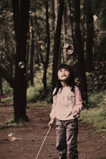 Girl looking at bubble in forest