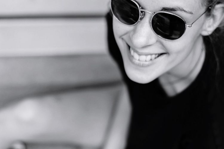 Close-up portrait of smiling young woman wearing sunglasses