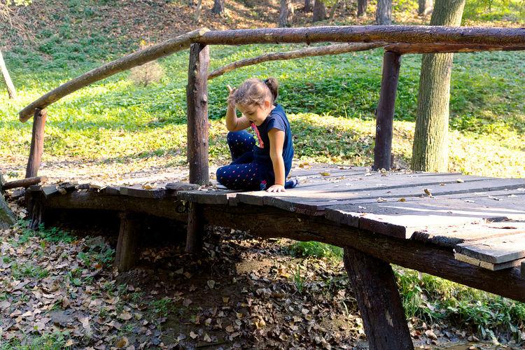 Full length of girl sitting on bench against trees