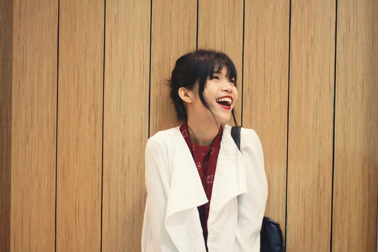 Young woman laughing against wooden wall