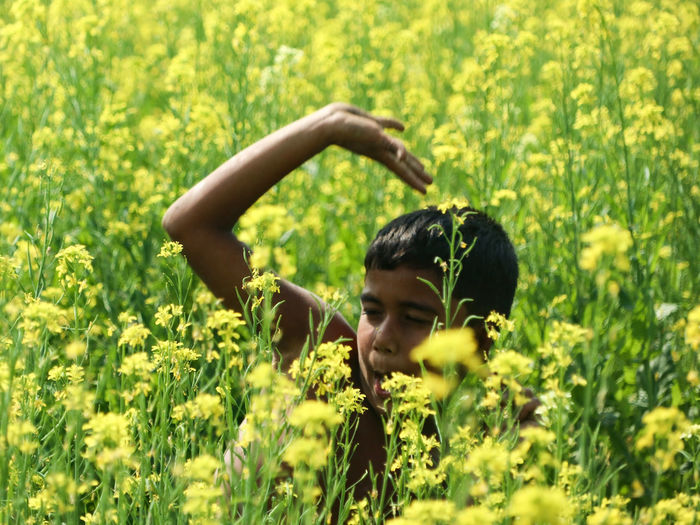 Young woman with yellow flower in field