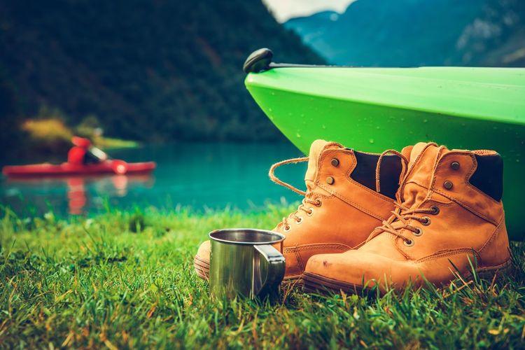Close-up of shoes and mug with kayak at lakeshore