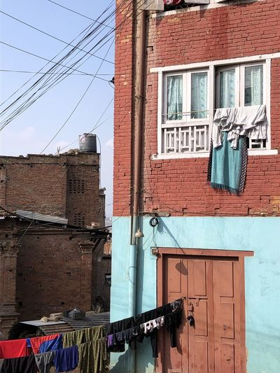 Low angle view of clothes drying on building against sky