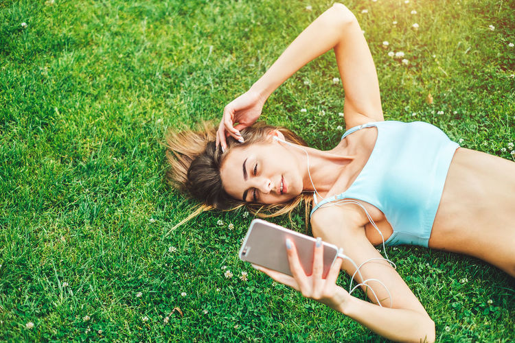 Grass Lying Down Wireless Technology Technology Plant Communication Portable Information Device Smiling Young Adult Women Relaxation One Person Connection Portrait Nature Leisure Activity Smart Phone Young Women Beautiful Woman Outdoors