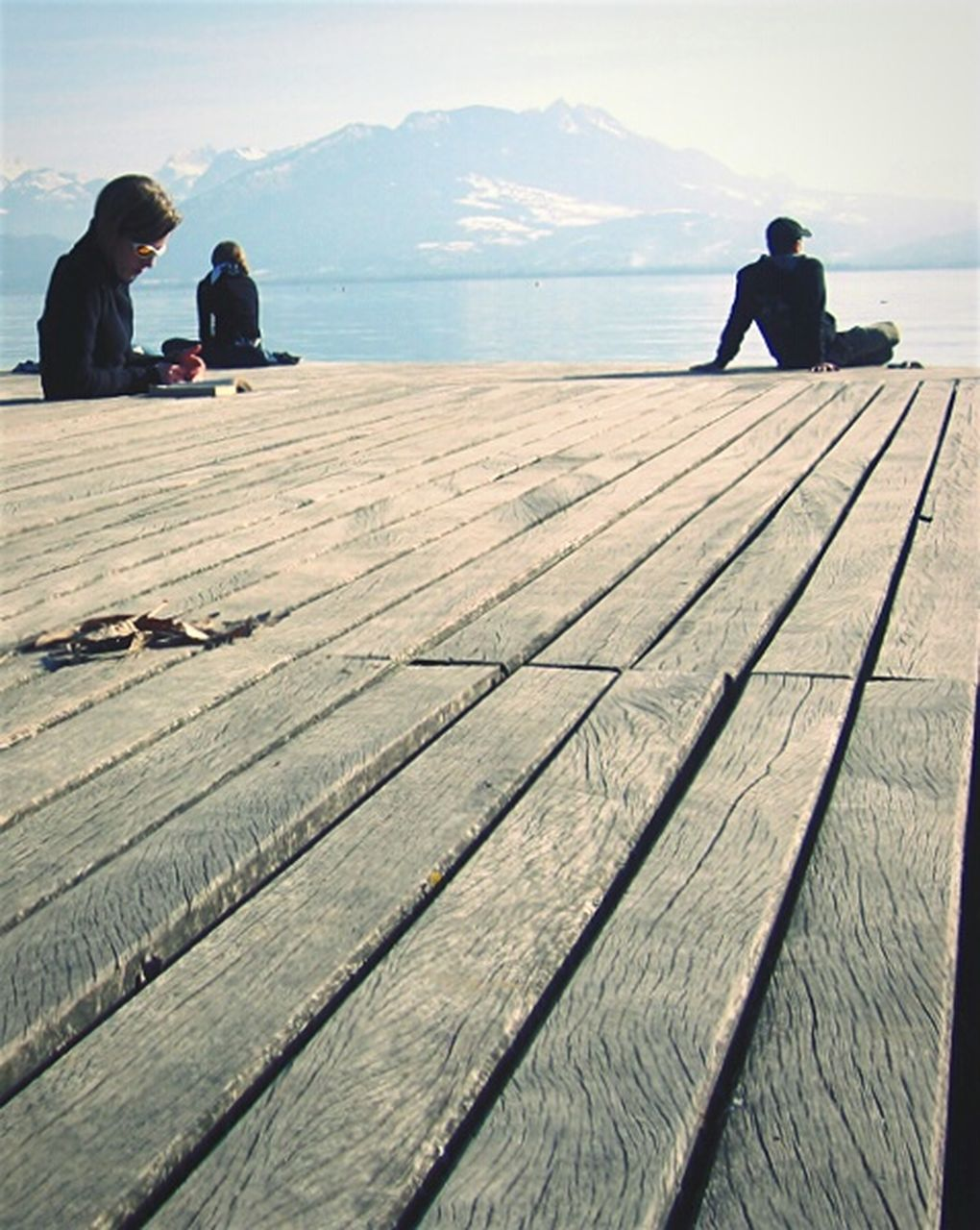 two people, real people, water, men, full length, togetherness, lifestyles, day, nature, leisure activity, outdoors, women, sitting, sea, mountain, scenics, beauty in nature, wood paneling, sky, young women, young adult, adult, people, adults only