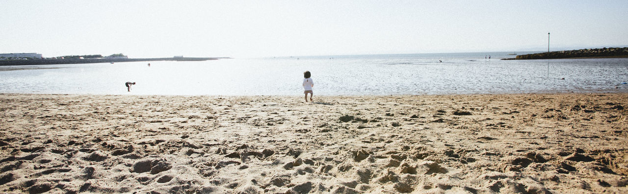 A toddler at Morecambe Beach, Lancashire, UK Adult Adults Only Beach Beauty In Nature Beauty In Nature Clear Sky Day Full Length Horizon Over Water Leisure Activity Nature One Person Outdoors People Real People Rear View Sand Scenics Sea Sky Standing Toddler  Tranquil Scene Tranquility Vacations Water