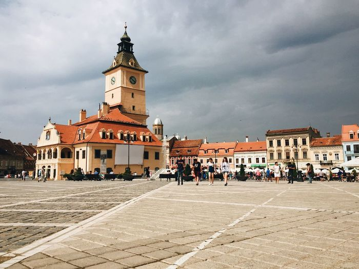 Clock tower at brasov council square against cloudy sky
