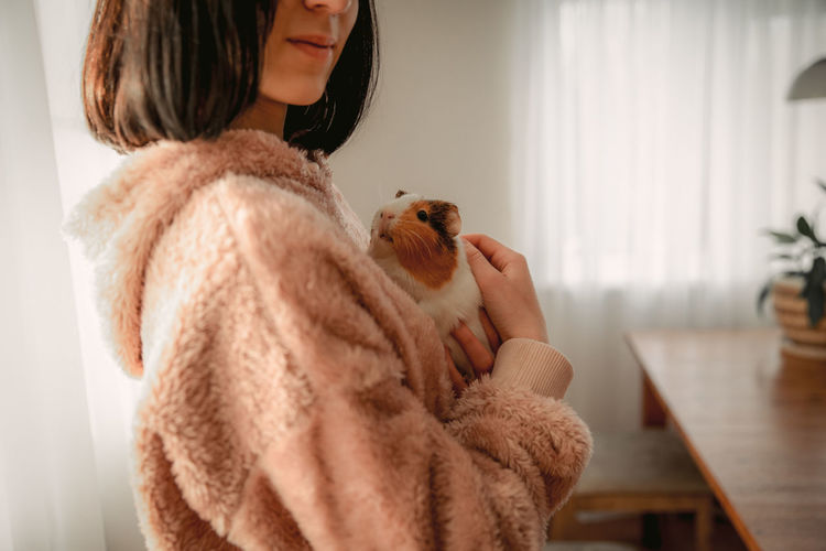 Midsection of woman holding toy at home