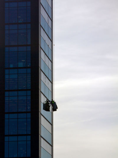Low angle view of window washer against cloudy sky