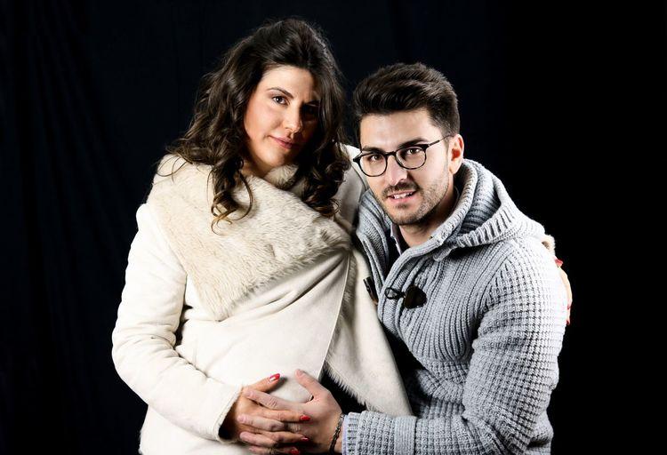 Portrait of couple against black background