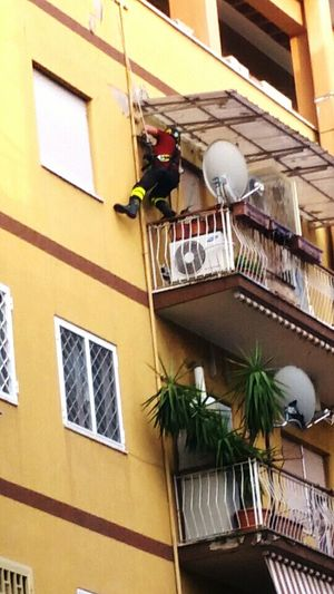 This scene happened in a dry summer afternoon. Bravery of the firefighter was to get a balcony 2 floors down the attic, to extinguish a fire started in an apartment, while its owners were away on vacation. The Photojournalist - 2016 EyeEm AwardsFirefighter Danger Height Saving Lives Roma Italia Pompiere Incendio The Photojournalist - 2017 EyeEm Awards