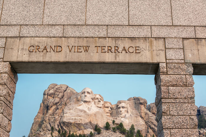 View of Mount Rushmore National Memorial and the entrance to the Grand View Terrace Abraham Lincoln George Washington Grand View Terrace Keystone Landmark Low Angle View Memorial Monument Mount Rushmore Mt Rushmore No People Outdoors Patriotic Patriotism Rock - Object Sculpture Sculptures Sky South Dakota Teddy Roosevelt Thomas Jefferson Tourism Travel Travel Destinations USA