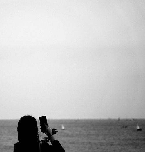 Man photographing at sea against clear sky