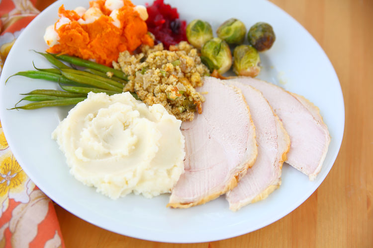 Traditional Thanksgiving dinner on white plate Balanced Meal Brussels Sprouts Close-up Colorful Cornbread Sausage Stuffing Day Freshness Green Beans Holiday Food Home Cooking Homemade Food Indoors  Mashed Potatoes Napkin Natural Light No People Ready-to-eat Serving Size Sweet Potatoes Textures Thanksgiving Dinner Traditional American Food Turkey Dinner With Trimmings White Meat White Plate