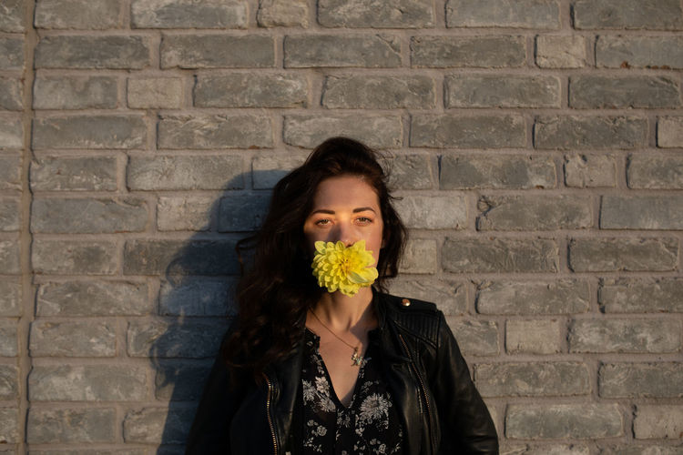 Portrait of woman with yellow flower in mouth against brick wall