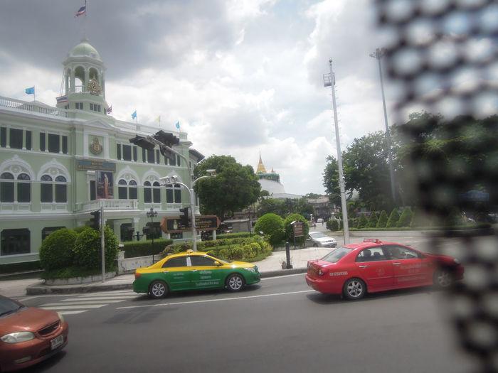 Cars on city street against cloudy sky