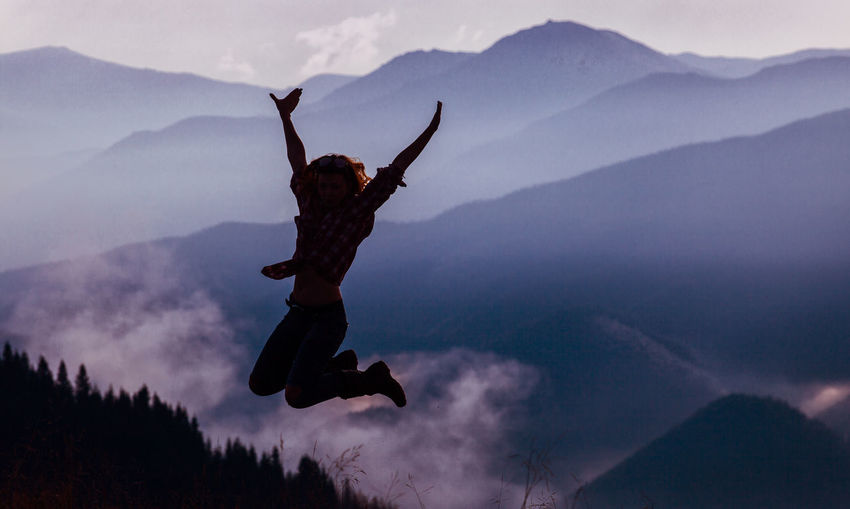Silhouette man jumping on mountain against sky
