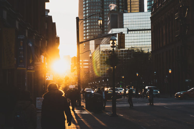 People walking on street amidst buildings against sky during sunset
