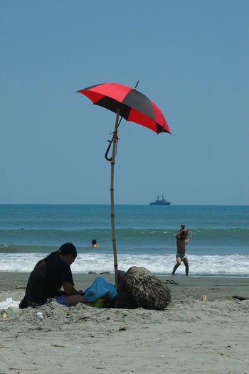 Woman sitting under umbrella tied to stick at beach
