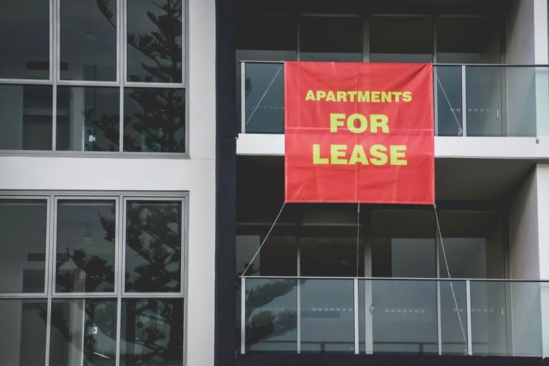 large red signage reading in yellow text Apartments For Lease hanging on the outside of an apartment block building Apartment Buildings Apartment Lease For Lease Real Estate Text Communication Western Script Glass - Material Built Structure Window Building Exterior Architecture Sign Building Reflection No People Information Capital Letter Day Information Sign Wall - Building Feature