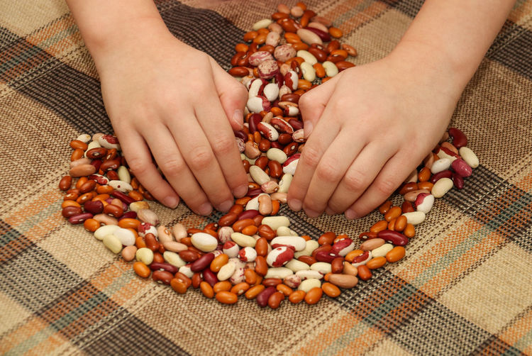Cropped hands of person holding nut food on table