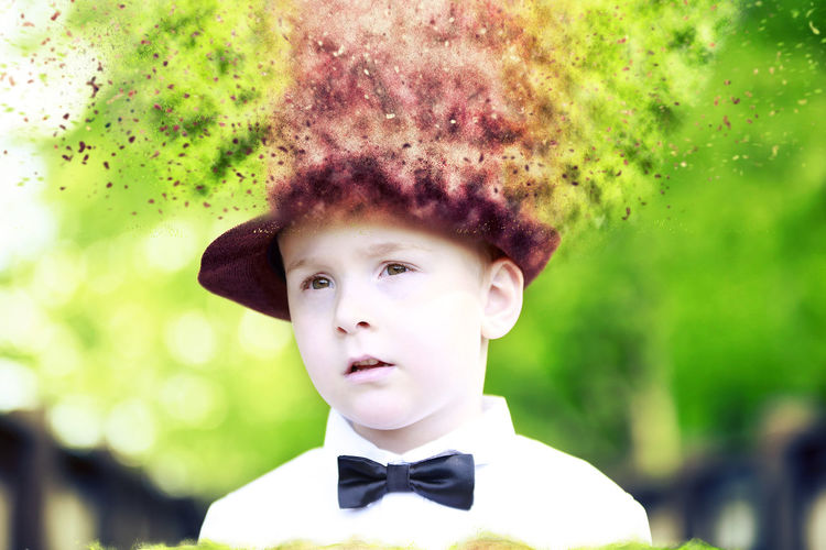 Close-up of boy wearing blurred hat outdoors