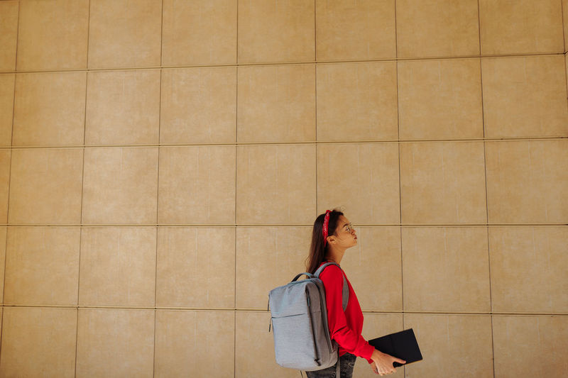Side view of woman standing against wall outdoors