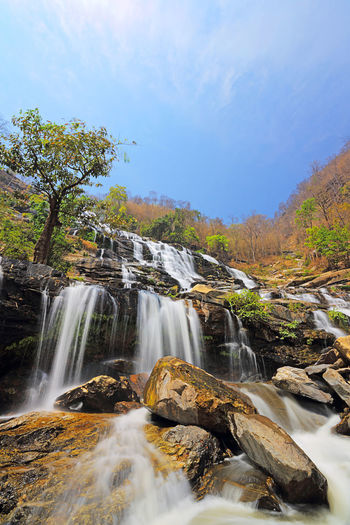 Beautiful view of Mae Ya Waterfall on hot sun day in the summer, northern of Thailand Scenics - Nature Water Flowing Water Beauty In Nature Rock Tree Waterfall Motion Rock - Object Solid Nature Long Exposure Forest Land Blurred Motion No People Plant Sky Environment Flowing Outdoors Power In Nature Stream - Flowing Water Falling Water Amazing Autumn Beautiful Mae Ya Waterfall Chiangmai Thailand Blue Cascade Landscape Yellow