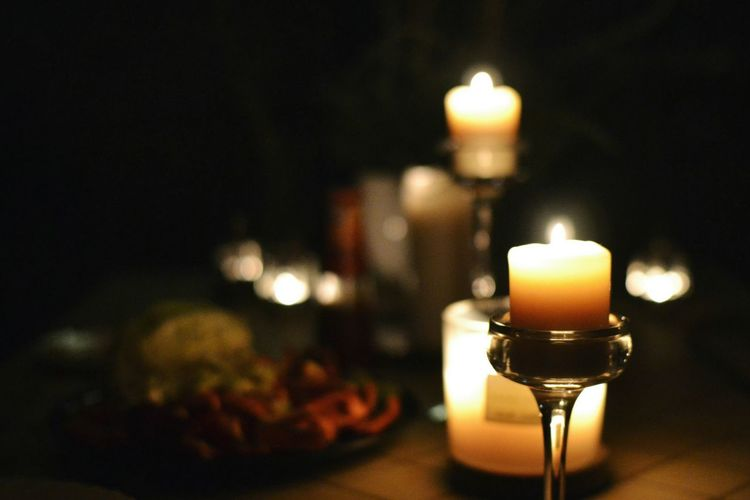 Lit Candles In Candlestick On Table