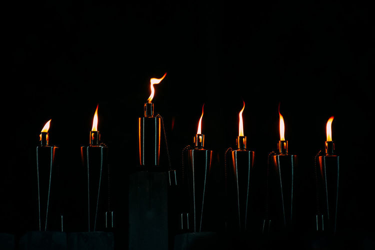 Close-up of illuminated cigarette lighters against black background